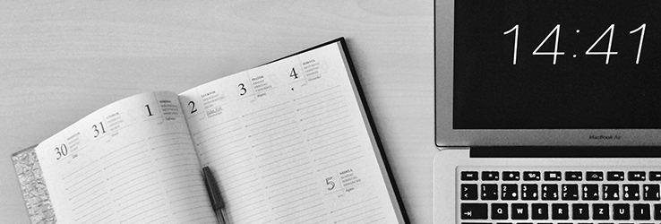 Foto van een laptop en agenda.